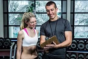 Berufshaftpflichtversicherung Fitnesstrainer – Fitnesstrainer bespricht Trainingsplan