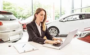 Betriebshaftpflichtversicherung Autohäuser - Autohändlerin am Laptop