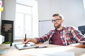Betriebshaftpflichtversicherung Grafiker – Grafiker mit Tablet