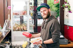 Betriebshaftpflichtversicherung Imbiss – Verkäufer mit Hotdog