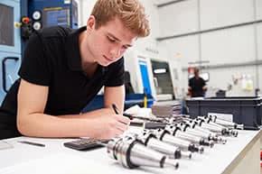 Betriebshaftpflichtversicherung Ingenieure – Junger Ingenieur untersucht Pläne