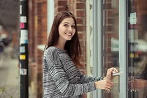 Betriebshaftpflichtversicherung Kleingewerbe – Junge Frau schließt ihren Laden auf