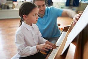 Betriebshaftpflichtversicherung Musikschule – Musiklehrer unterichtet am Klavier