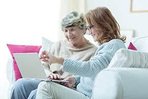 Betriebshaftpflichtversicherung Seniorenbetreuung – Junge Frau erklärt Seniorin etwas am Laptop