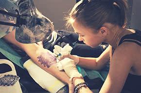 Betriebshaftpflichtversicherung Tattoostudio – Tattoowiererin bei der Arbeit