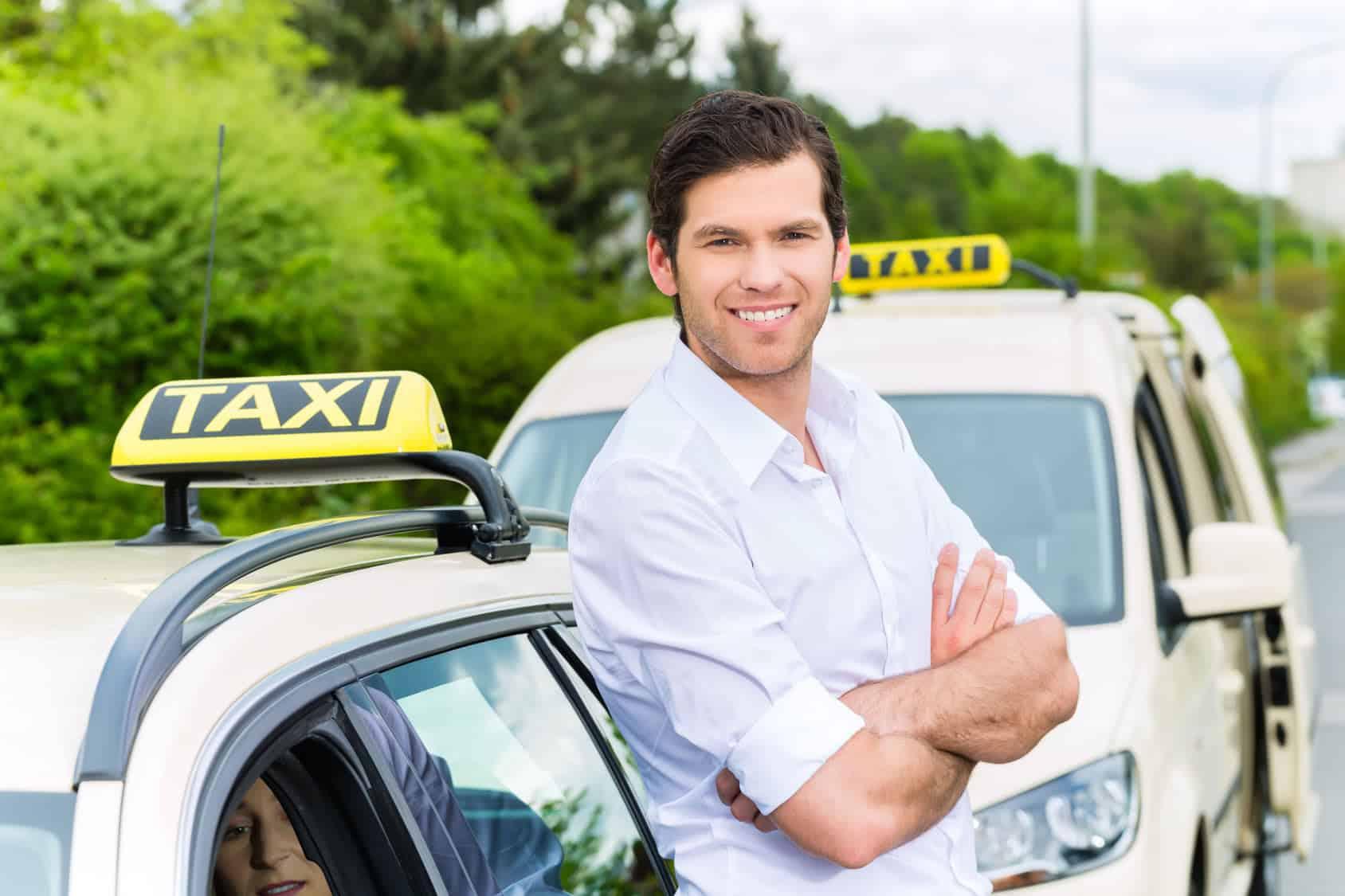 Betriebshaftpflichtversicherung Taxiunternehmen – Taxifahrer neben Taxi wartet auf Kunden