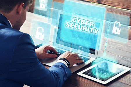 Cyber Risk Versicherung - Geschäftsmann am PC
